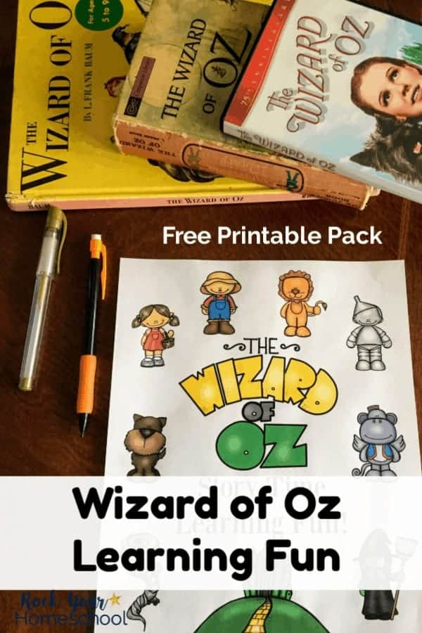 Free printable Wizard of Oz Learning Fun pack on dark wood desk with gold pen & orange mechanical pencil and Wizard of Oz books & DVD case