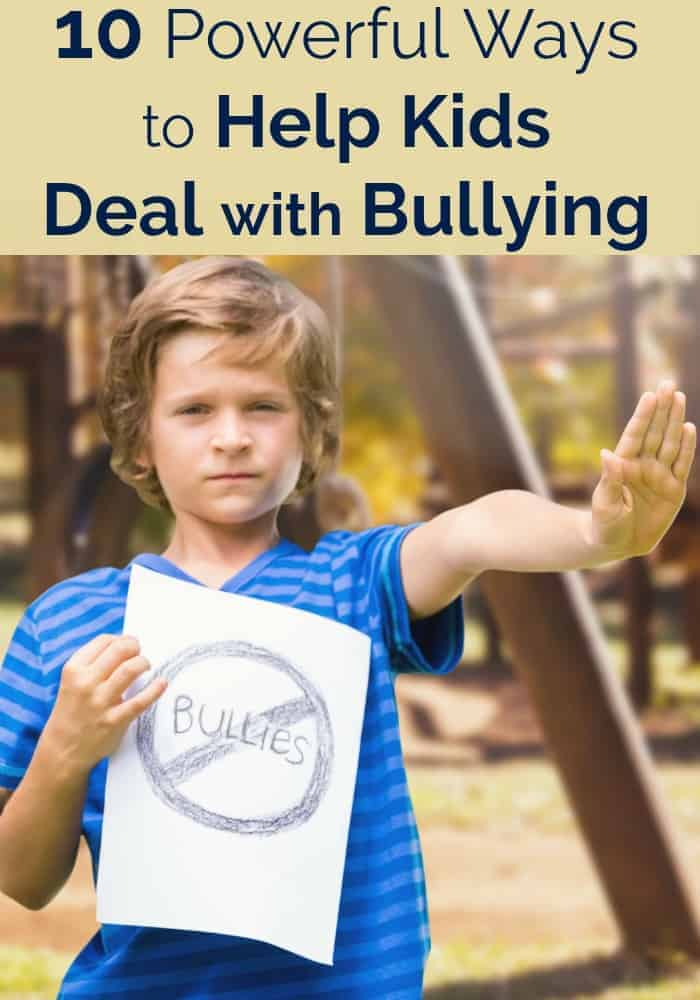 Young boy on playground holding up anti-bullying sign with his hand raised