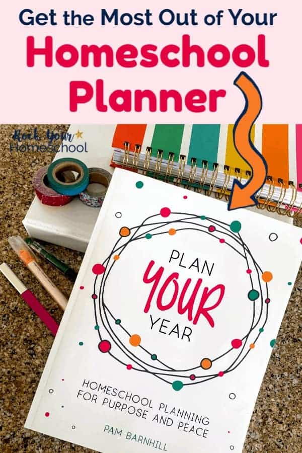 Plan Your Year book with white 3-ring binder, Living Well Planner striped, washi tapes, and pens on granite surface