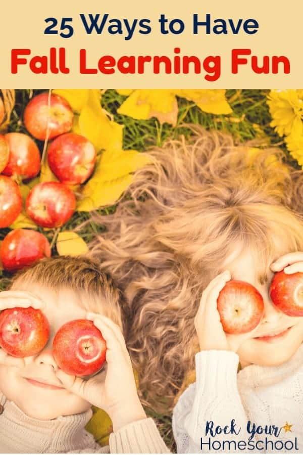 Boy & girl with apples covering eyes & smiling laying on grass by pile of apples & gold leaves