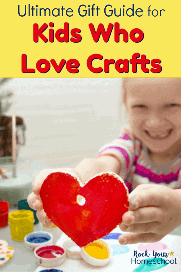 Young girl holding red painted heart craft with craft supplies in background