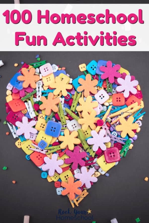 Rainbow of button, paper clips, clothespins, & candy in shape of a heart on a black chalkboard background