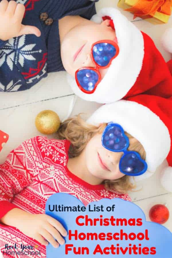 Brother & sister are smiling as they wear blue sparkly sunglasses & red Santa hats as they lay on a white wooden floor with Christmas tree decorations, gold present. The brother is is giving a thumbs up sign as his sister holds a blue paper mitten.