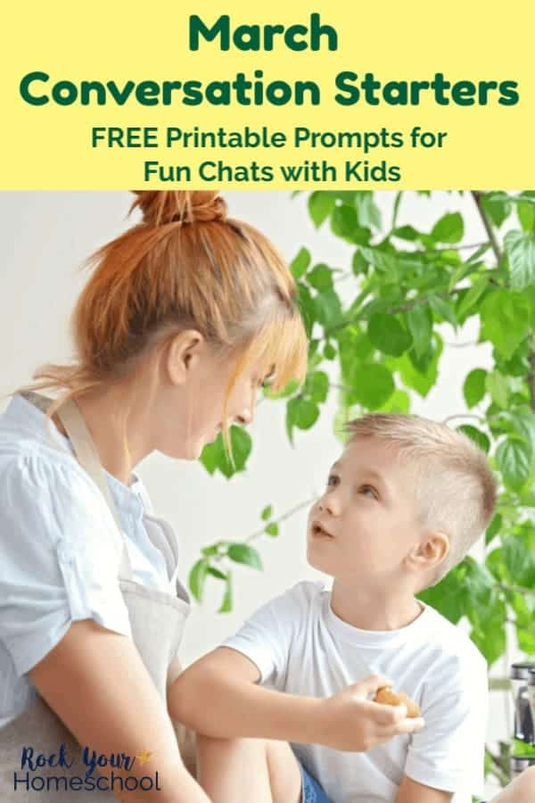 Red-haired mom with bun wearing white T-shirt talking with boy wearing white T-shirt in front of potted plant & white background