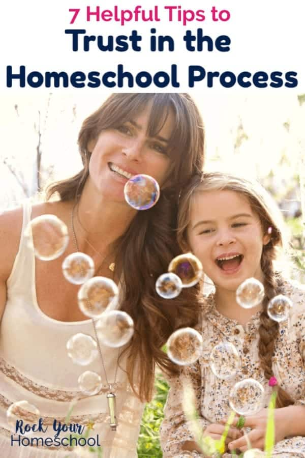 Mom & daughter dresses smiling & hugging as they watch bubbles float in the air