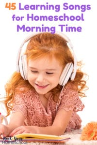 Red-haired girl smiling as she wears white headphones & listens to learning songs while using a blue pencil to write in a notebook with a mug with red heart & brown teddy bear