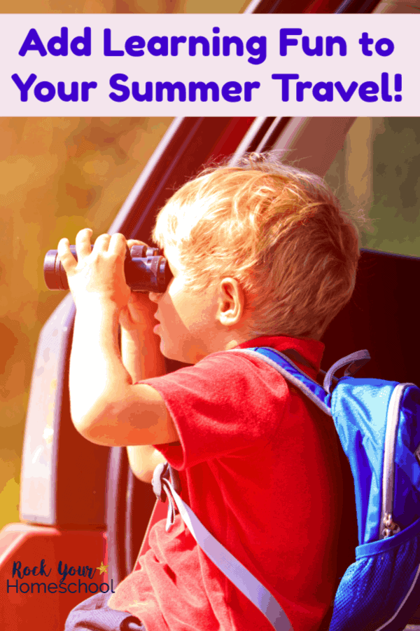 Boy wearing red shirt using black binoculars looking out car window