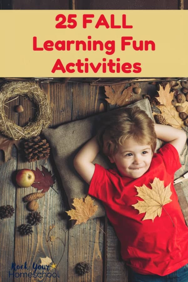 Young boy in red shirt laying down with hands behind head & smiling with a leaf on his chest & leaves, pinecones, wreath, & apples on wood background for Fall learning fun