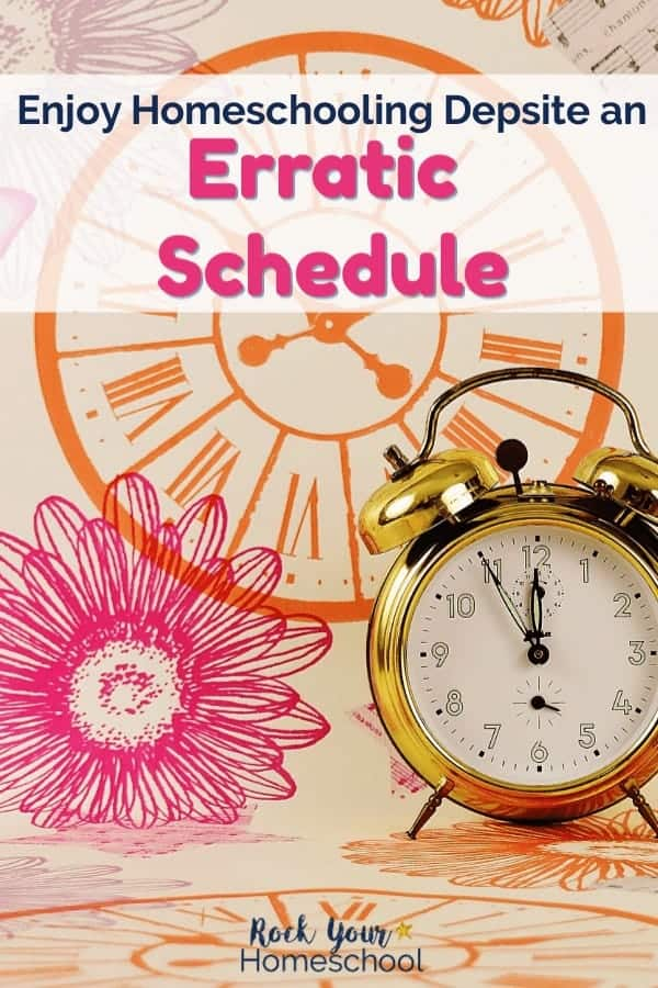 Gold alarm clock on printed background with orange roman numeral clock, pink flower
