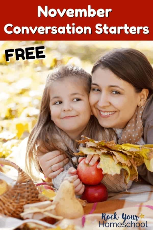 Mother & daughter holding leaves & apples as they smile while having November fun chats