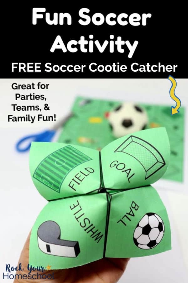 Woman's hand holding a soccer cootie catcher featuring a field, goal, whistle, & ball with blue scissors, soccer cootie catcher printable page, & small toy soccer ball in background
