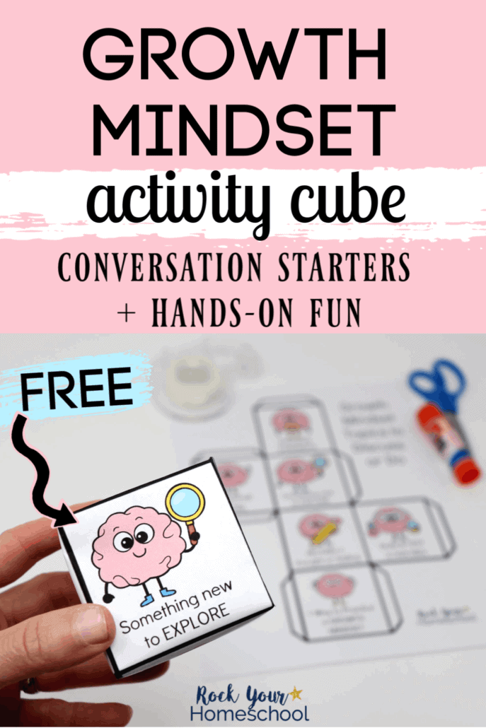 Woman holding growth mindset cube with printed page, glue stick, & blue scissors in background to feature the amazing hands-on & interactive ways to boost growth mindset skills with these conversations starters for kids