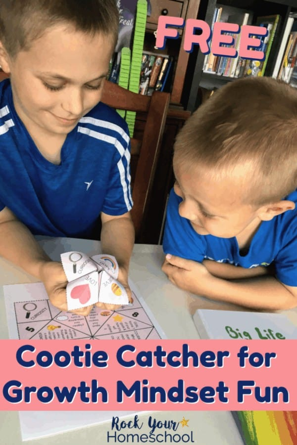 Two boys smiling as they use a growth mindset cootie catcher to learn & practice growth mindset skills