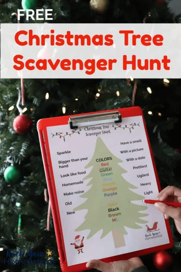Boy holding red pen & Christmas Tree Scavenger Hunt printable on red clipboard in front of Christmas tree