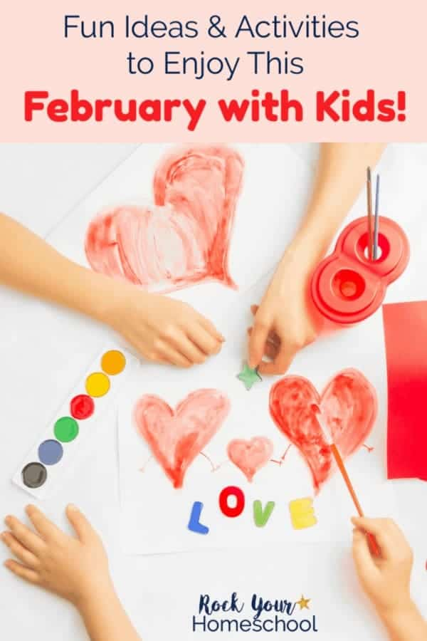 The hands of two kids using watercolor paints to make hearts & red paper & magnet letters spelling love on white background