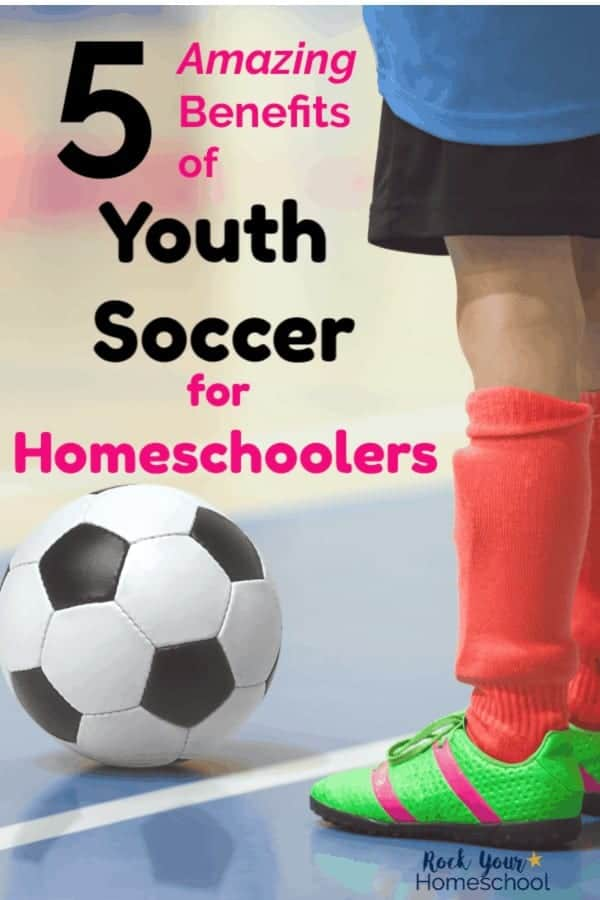Youth soccer playyer wearing blue shirt, black shorts, orange soccer socks, bright green & pink-stripe cleats on hard surface with black & white soccer ball