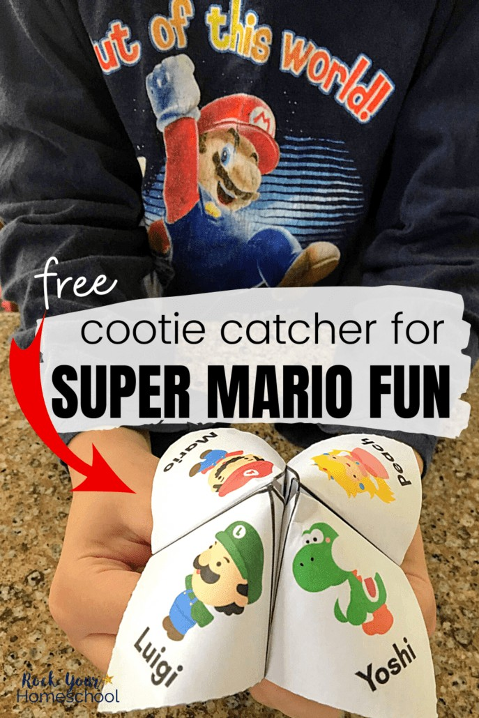 Boy holding Super Mario cootie catcher & wearing a Super Mario shirt to feature the amazing fun your kids will have with this free cootie catcher