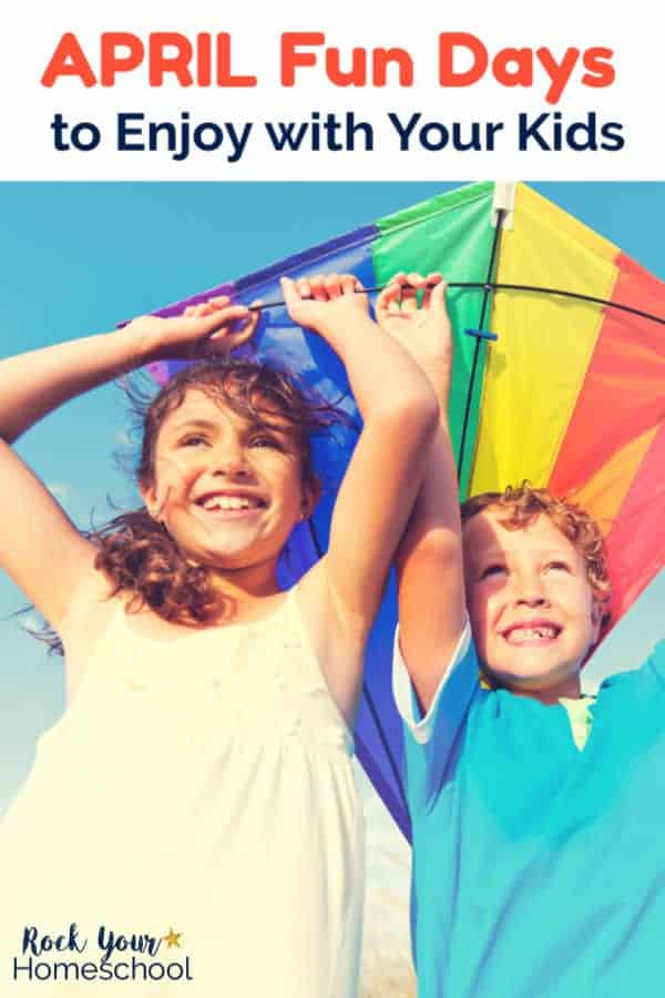 Sister & brother smiling and holding a rainbow kite with blue sky background for April Fun