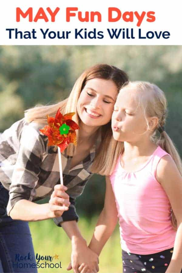 Mom & daughter smiling as daughter blows on pinwheel with trees & grass in background