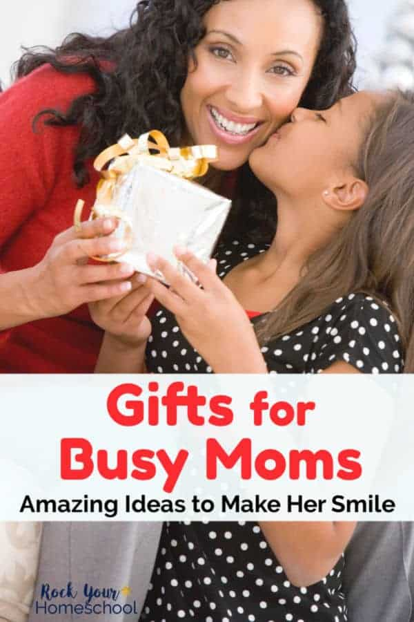 Smiling woman with dark curly hair & wearing red sweater is being kissed on the cheek by her daughter wearing a black & white polka dot dress & giving her mom a gift with gold wrapping paper & bow
