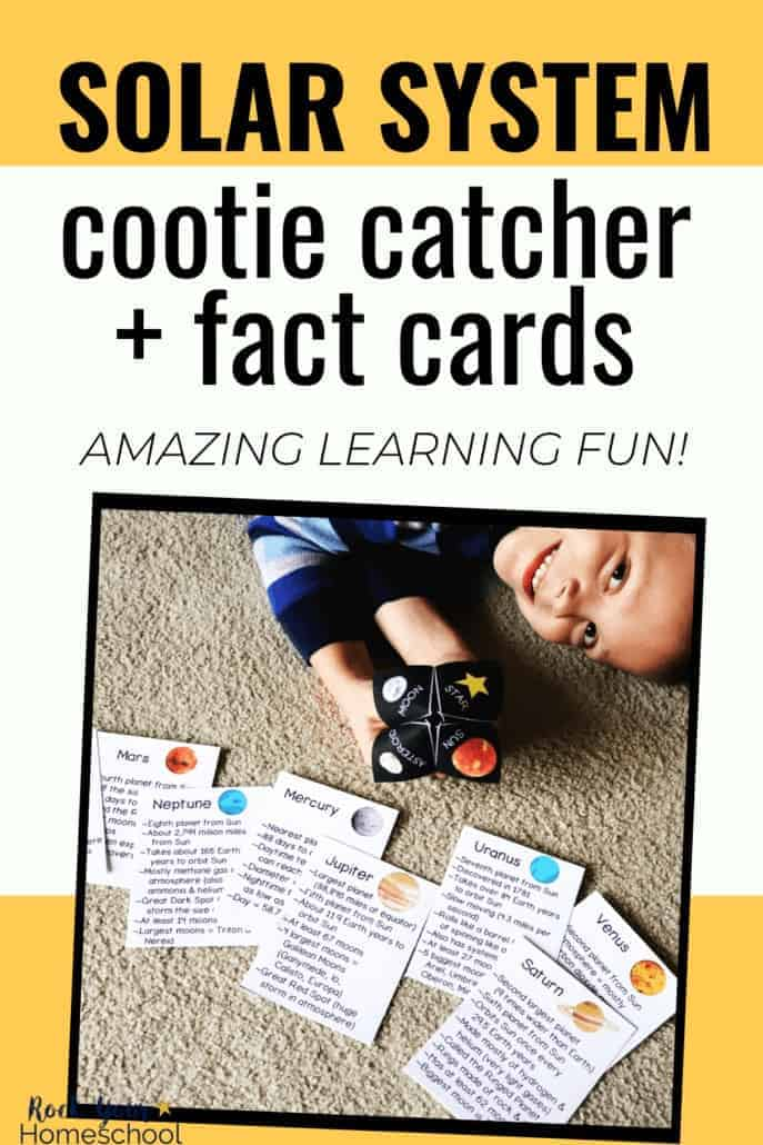 Boy smiling and holding solar system cootie catcher with planet fact cards in front of him on the carpet to feature the science learning fun to be had with this activity pack