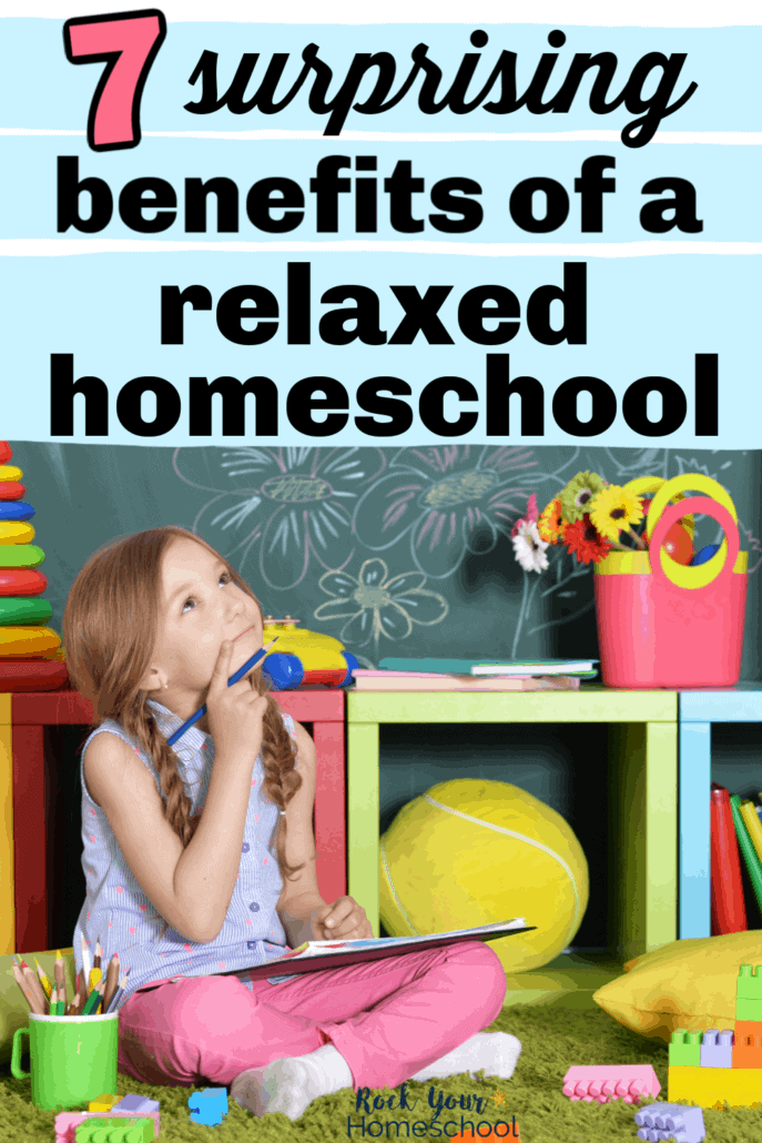 Girl smiling & looking up at a chalkboard with doodles & surrounded by books & learning resources to feature the 7 surprising benefits of a relaxed homeschool style
