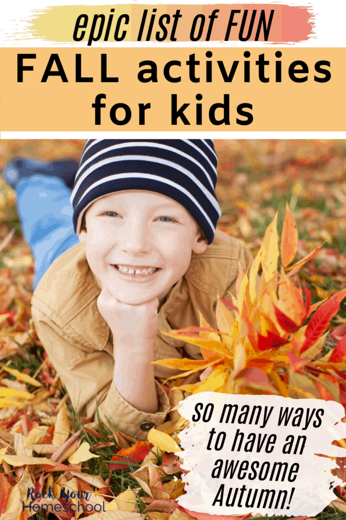 Boy smiling with a navy striped hat on & laying in leaves to feature this epic list of fun Fall activities for kids and families