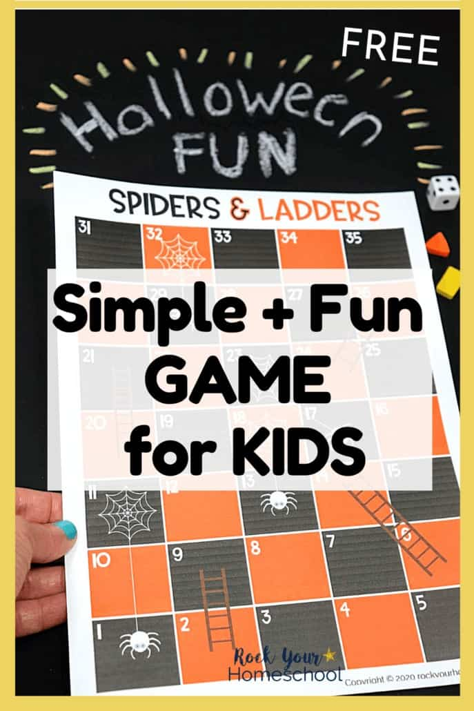 Woman holding Spiders and Ladders game board with Halloween Fun written on black chalkboard to feature the amazing fun you'll have with this free Halloween game for kids