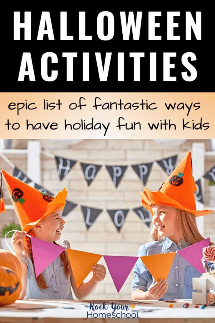 Two girls smiling at each other & wearing jack o' lantern hats as they hold purple & orange banner to feature this epic list of Halloween activities for kids that you can use to make this holiday special this year.
