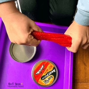Boy using Crazy Aaron's Thinking Putty (Angry Putty version) as a creative and fun homeschool tool