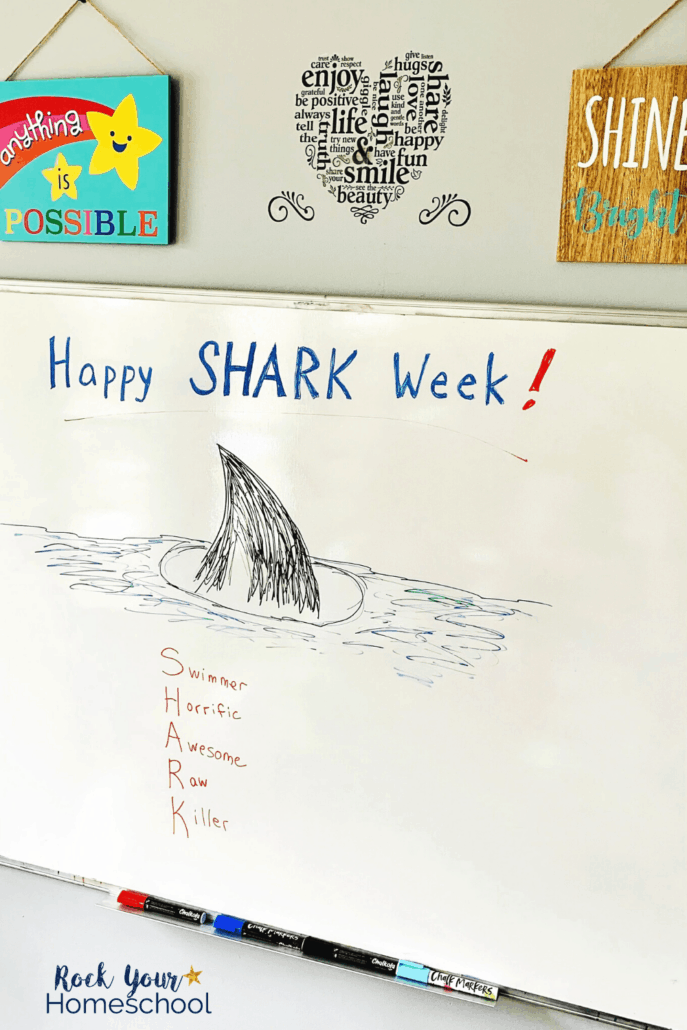 Whiteboard with Happy Shark Week & shark fin drawn with chalk markers to feature these cool school art supplies