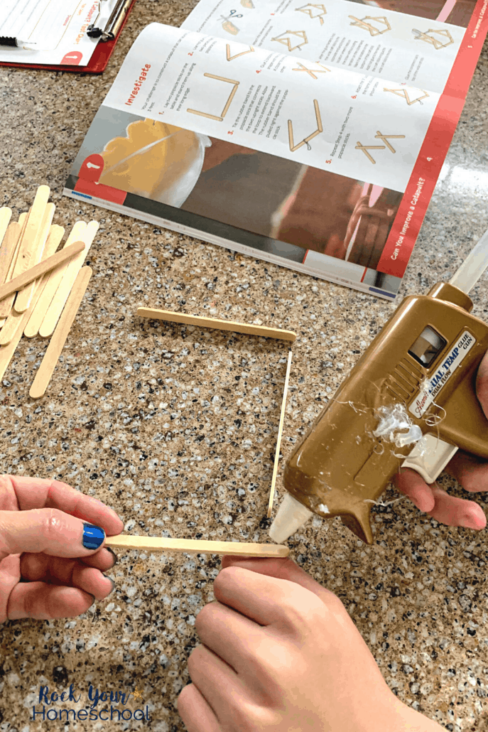 Tween boy using hot glue gun to build a catapult out of popsicle sticks and rubber bands to show the awesome science activities found in BookShark Science packages